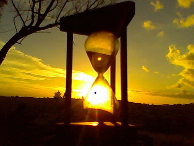 De fundo um lindo pôr do sol, como imagem de primeiro plano temos uma ampulhete.